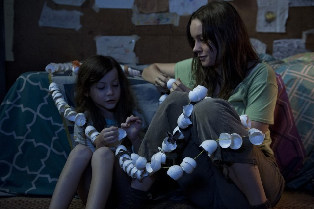"Joy Newsome (Brie Larson) and her son Jack (Jacob Tremblay) pass the time in confinement by stringing together egg shells in ""Room."""