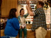 "Roseanne and Dan aid an injured Darlene in the pilot episode ""Life and Stuff."""