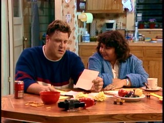Dan (John Goodman) and Roseanne (Roseanne Barr) look it over in their kitchen.