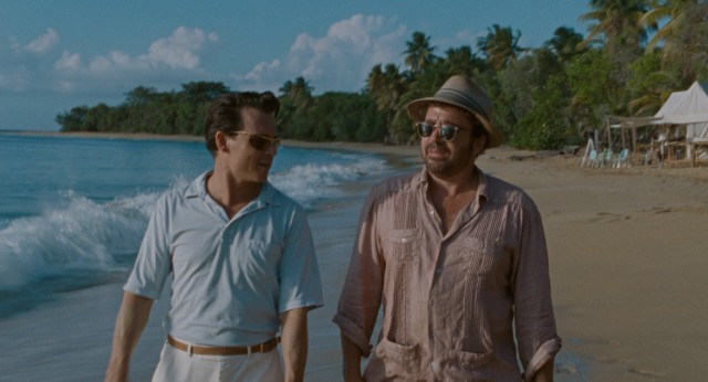 Paul Kemp (Johnny Depp) and Bob Sala (Michael Rispoli) go for a sunset walk on the shore of an uninhabited Puerto Rican island being developed.