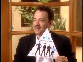"Tom Hanks fondly recalls The Rutles' triangular album, which he holds up in ""Can't Buy Me Lunch."""
