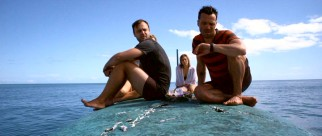 Sitting atop their capsized yacht, Matt and Kate weigh their options, while Luke checks his watch.