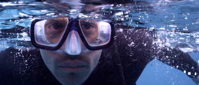 Luke (Damian Walshe-Howling) puts on his scuba mask to look beneath the surface, as we fear he'll see a shark.