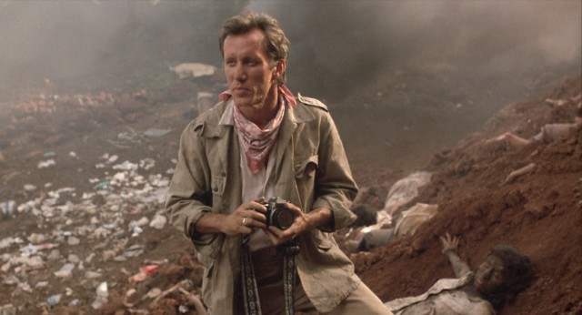 "Richard Boyle (James Woods) photographs a dump site used by the inhumane military regime in Oliver Stone's ""Salvador."""