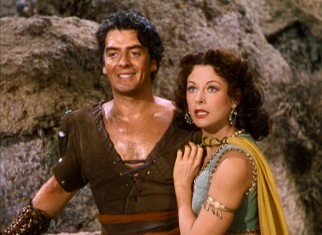 Delilah (Hedy Lamarr) clings to the strong arms that Samson (Victor Mature) used to slay a lion.