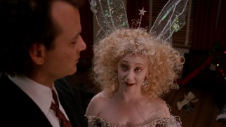 Frank is hit with knowledge and a toaster by the winged, violent Ghost of Christmas Present (Carol Kane).