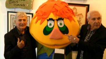 Sid (left) and Marty Krofft pose for photos with H.R. Pufnstuf between them at a 2010 Los Angeles event documented here.
