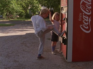 Kids find a way to kick free soda cans out of this Coca-Cola vending machine which they proceed to sell at half-price.