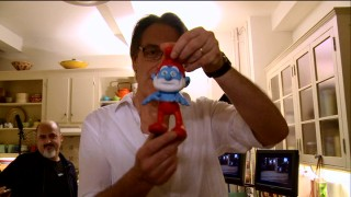 "Director Raja Gosnell shows off his poseable Papa Smurf placeholder used in filming in ""Comic Book to the Big Screen."""
