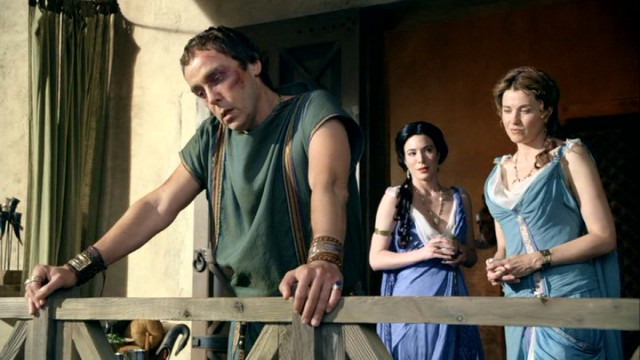 A bruised Quintus Lentulus Batiatus (John Hannah) looks out over his ludus, while Gaia (Jaime Miller) and Lucretia (Lucy Lawless) stand back.
