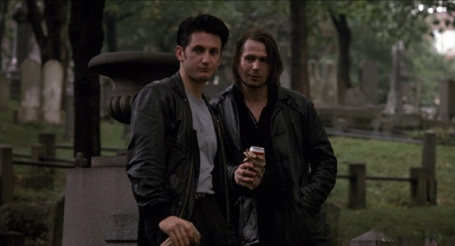 "From a distance, Terry Noonan (Sean Penn) and Jackie Flannery (Gary Oldman) look in on the cemetery burial of a slain friend in the 1990 crime drama ""State of Grace."""