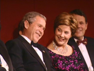 Laura Bush makes sure her husband President George W. Bush is laughing at Steve Martin's jokes about him in The Kennedy Center's tribute to Paul Simon.