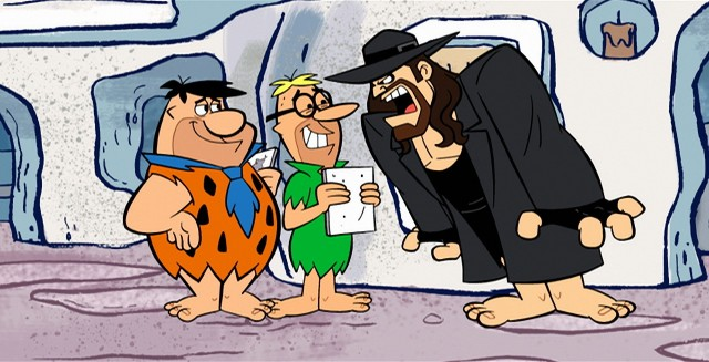 "The Undertaker uses his outdoor voice on Fred Flintstone in ""The Flintstones and WWE: Stone Age Smackdown."""