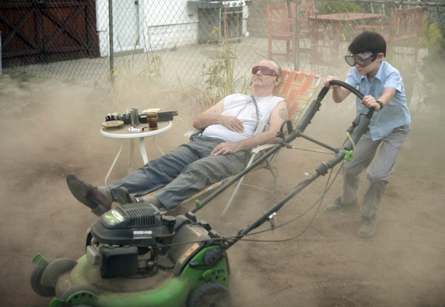Oliver Bronstein (Jaeden Lieberher) trudges up clouds of dirt in mowing the backyard of little grass in the backyard of his next-door neighbor and babysitter Vincent MacKenna (Bill Murray).