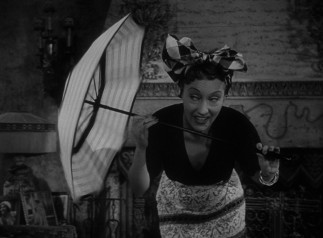 Norma Desmond (Gloria Swanson) performs a comedy routine with blinking eyes and a twirling umbrella for her young houseguest.