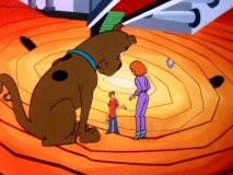 The journey inside a mirror takes the gang to a strange place where Scooby gets bigger, towering over Shaggy and Daphne.