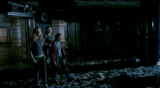 Scarlet leads Andy and Tammy through a darkened, abandoned London train station.