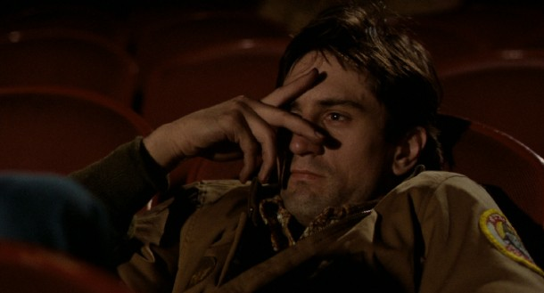 "Travis Bickle (Robert De Niro), ""God's lonely man"", watches an X-rated movie in solitude with one eye covered."