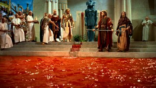 Moses demonstrates the power of his God to Rameses with a staff turning water into blood, the first of ten plagues befalling Egypt.