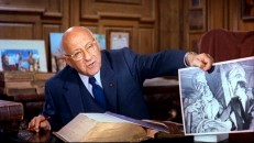 Producer/director/showman Cecil B. DeMille displays a photograph of Charlton Heston looking at Michelangelo's Moses statue in a 10-minute trailer for the movie.