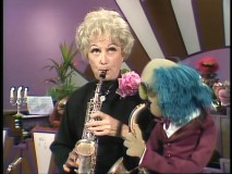 "Phyllis Diller and Zoot compare their saxophone skills in an unusual performance of ""The Entertainer."""