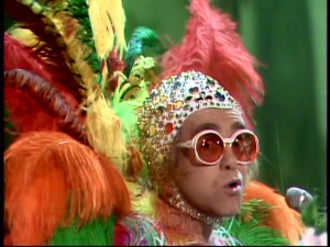 No need to adjust your television. Elton John merely brings out all the bright colors and glitzy wardrobe touches.