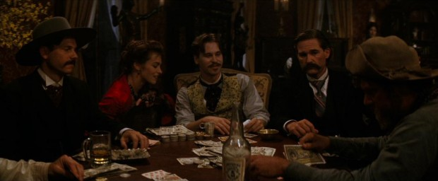 "Doc Holliday (Val Kilmer) and his gal (""Big Nose"") Kate (Joanna Pacula) are amused by the growing frustration of Ike Clanton (Stephen Lang, far right) in his poker game with Morgan (Bill Paxton) and Wyatt Earp (Kurt Russell)."
