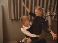 "Dakota Fanning carries younger sister Elle around the studio and ""Behind the Microphone."""