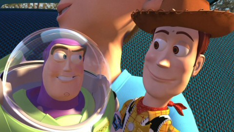 Safe in Andy's arms, Buzz and Woody sneak a knowing glance at each other.