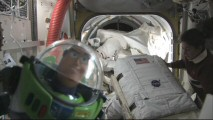 "In ""Buzz Lightyear Mission Logs"", America's favorite space ranger poses for the camera onboard the NASA shuttle as astronauts pull out their suits."