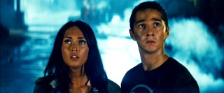 Mikaela (Megan Fox) and Sam (Shia LaBeouf) look up at the Transformers around them.