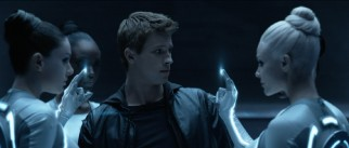 Sam Flynn (Garrett Hedlund) gets a welcome from four Sirens, who strip his clothes with their lighted fingers to dress him in the fashion of the alternate world.