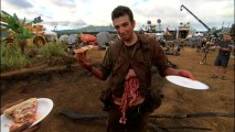 "Though his guts would appear to be pouring out, Jay Baruchel still enjoys a slice of pizza with a smile in ""The Hot LZ."""