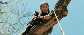 Mattie Ross (Hailee Steinfeld) tests her true grit with a tree climb and rope cut to identify a hanged man.