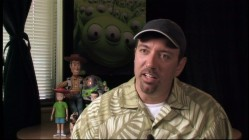 "Art designer Ralph Eggleston reflects on the film's look in ""Designing 'Toy Story.'"" Lucky guy gets to pose in front of figure of Andy and Sid that clearly haven't been released to the general public."