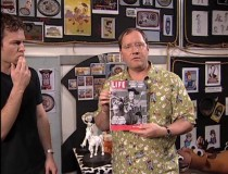 "John Lasseter shows off an old issue of Life magazine, one of many cool ""Woody's Roundup"" props created purely for TS2."
