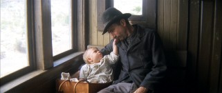 On a train ride in 1902 America, newly-adopted infant H.W. Plainview tugs at the whiskers of his prospector-turned-oil man father (Daniel Day-Lewis).