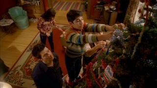 Daniel watches as Justin (Mark Indelicato) puts up a Christmas tree ornament, something he himself likely never did in his esteemed home.