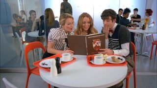 Kimmie (Lindsay Lohan) shows off her old yearbook to Amanda (Becki Newton) and Marc (Michael Urie), embarrassing Betty photos and all.