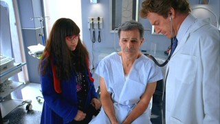 Betty (America Ferrera) looks on as a miserable Ignacio (Tony Plana) has his cough checked by Dr. Farber (Kevin Kilner).