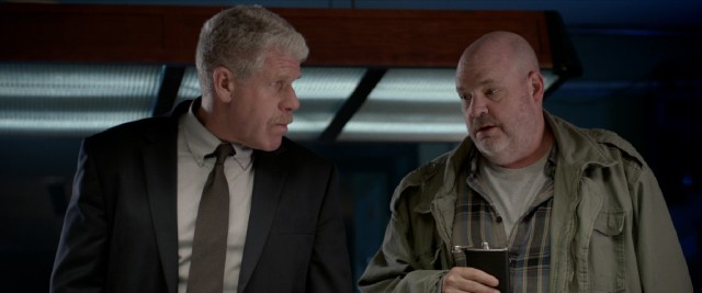Detective Chilcoat (Ron Perlman) takes genuine interest in the crazy conspiracy claims of Vogler (Pruitt Taylor Vince).
