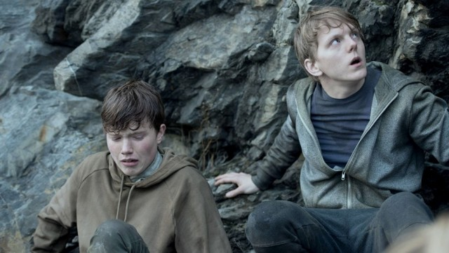 "Viljar Hanssen (Jonas Strand Gravli, right) and friend hide on the side of a cliff while a gunman attacks their Utøyan summer camp in ""22 July."""