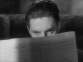 Hannay (Robert Donat) learns that he is wanted for murder from a fellow train passenger's newspaper.