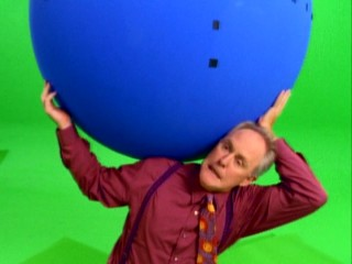 "John Lithgow has got the whole world in his hands (plus a French Stewart sitting on top) in this green screen promo shoot seen in ""A Glimpse Behind-the-Scenes."""