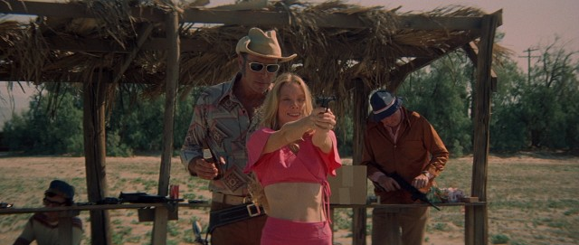 The new and improved Pinky Rose (Sissy Spacek) takes shooting range target practice with cowboy Edgar (Robert Fortier), much like Millie did before her.