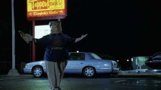 Using bags for a mask and a pretend gun, Tammy (Melissa McCarthy) practices her stick-up skills in a Topper Jack's parking lot.