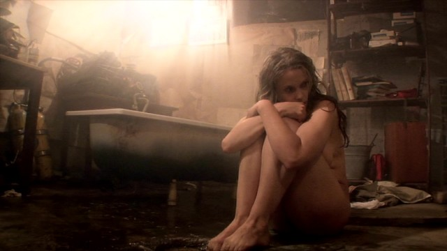 The tailless present-day Thale (Silje Reinåmo) curls up in a fetal position next to her milky bathtub.
