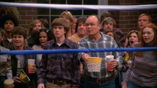 Father (Kurtwood Smith) and son (Topher Grace) enjoy a wrestling match together ringside.