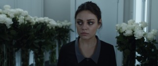 Gloomy New York hotel maid Julia (Mila Kunis) is not pleased by the many white flowers she is supposed to move to another room.