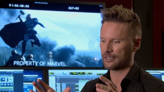 "Composer Brian Tyler discusses his ""Dark World"" score in front of a freeze frame from the film and many computer screens."